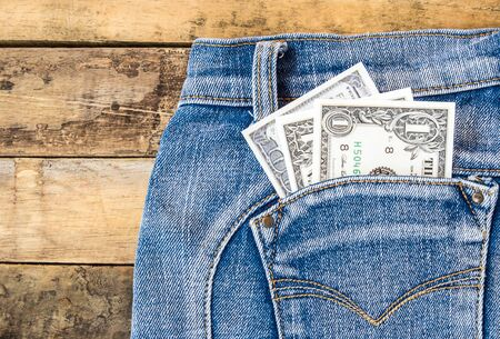 Dollar money in pocket blue jeans on wooden background
