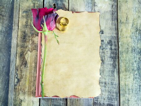 red roses: Fresh red rose and old paper on wooden background. Holidays romantic background
