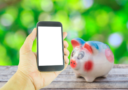 Hand holding smart phone on piggy bank on wooden table over blurred background photo