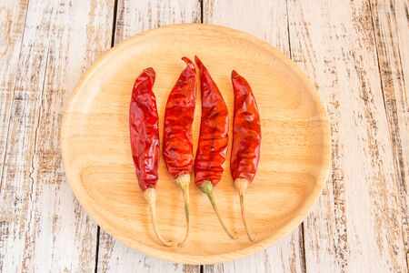 chili peppers: Dried chili peppers in wooden plate on white wooden background