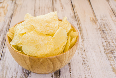 nosh: Potato chips in wooden bowl on white wooden table background
