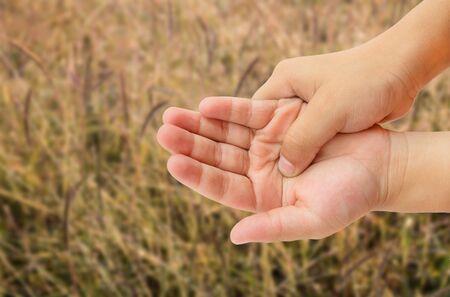 douleur main: Close up douleur de main avec de l'herbe comme un arri�re-plan flou soleil du matin