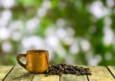 tabel: Coffee cup and coffee beans on wooden tabel with green nature background. blurred background