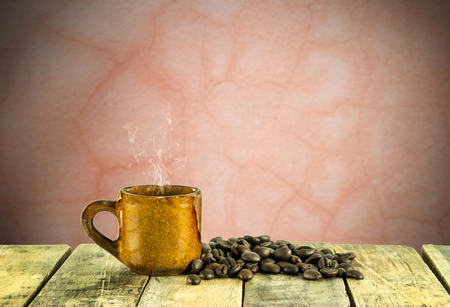 crack: Coffee cup and coffee beans on wooden table with blurre grunge background Stock Photo