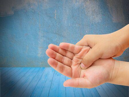 douleur main: Close up douleur de main au plancher en bois bleu avec floue grunge