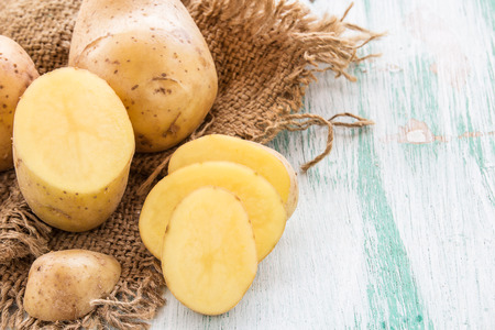 Sack fresh organic potatoes on a wooden table background