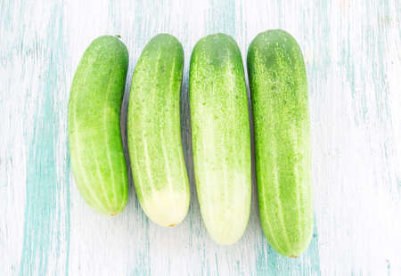 Fresh cucumbers on the wooden background