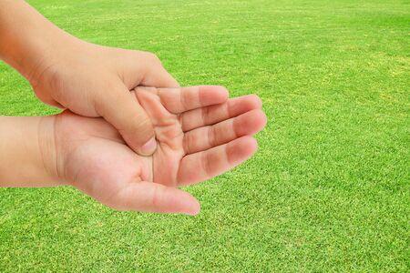 douleur main: Fermez jusqu'� la douleur de main sur fond d'herbe verte Banque d'images