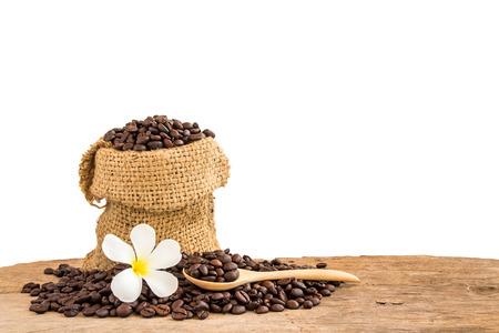 木製の分離の白い背景の上の黄麻布の袋のコーヒー豆