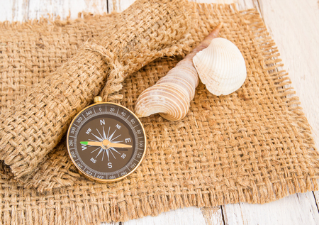 drawing compass: Compass and seashell on burlap sack on wooden background Foto de archivo