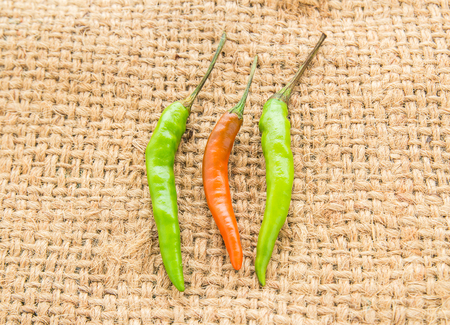 sackcloth: Red and green chili pepper on a sackcloth background Stock Photo