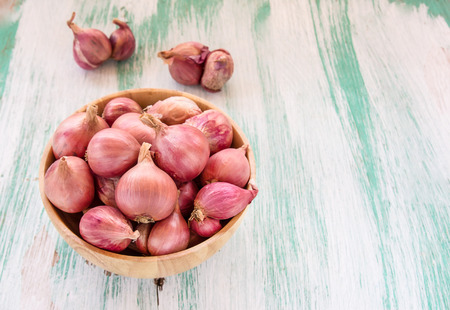 pealing: Fresh organic red onion in wooden bowl on wooden background