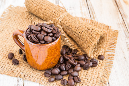 Coffee cup and coffee beans with burlap sack on wooden background