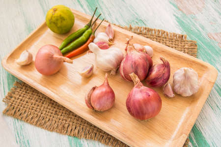 pealing: Fresh organic red onion in wooden plate on wooden background Stock Photo
