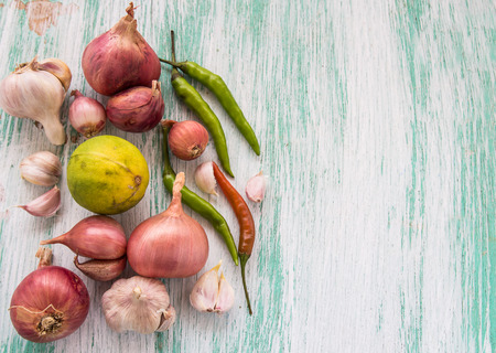 pealing: Fresh organic red onion garlic and chili on wooden table background