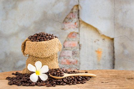 Coffee beans in burlap sack on wooden table with blurred grunge cracked background