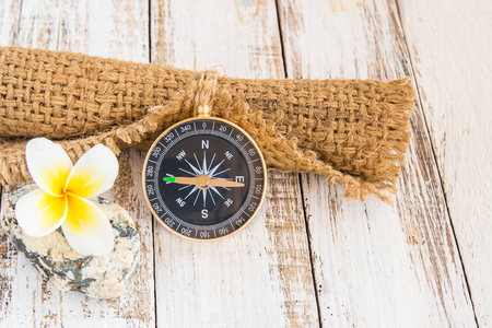 Close up compass and burlap sack on a wooden background