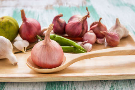 pealing: Fresh organic red onion garlic and lemon on a wooden background