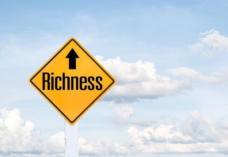 richness: Yellow traffic sign text for richness with blue sky background Stock Photo