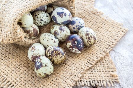 burlap sack: Quail eggs in burlap sack on a wooden table background