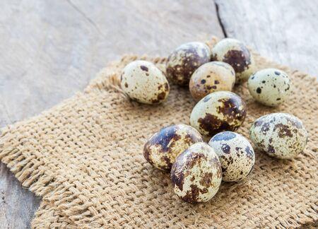 huevos de codorniz: Huevos de codorniz en saco de arpillera en un fondo de la tabla de madera Foto de archivo