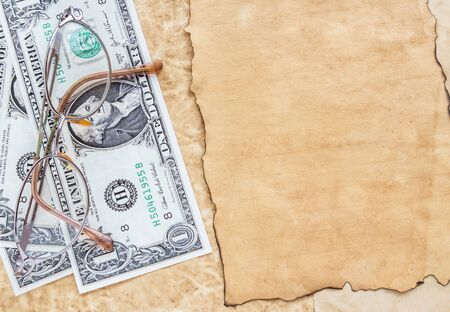 The dollar banknotes and eyeglasses on old paper background Banco de Imagens