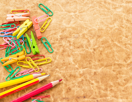 Colorful pencil and paperclips on old paper background for any design