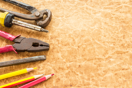 Tools and pencil on old paper background for any design