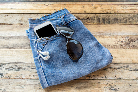 earphone: White earphone, sunglasses, smart phone and blue jeans on wooden table background