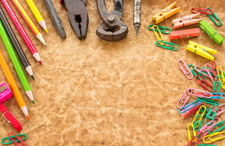 Tools, pencil and paperclips on old paper background for any design