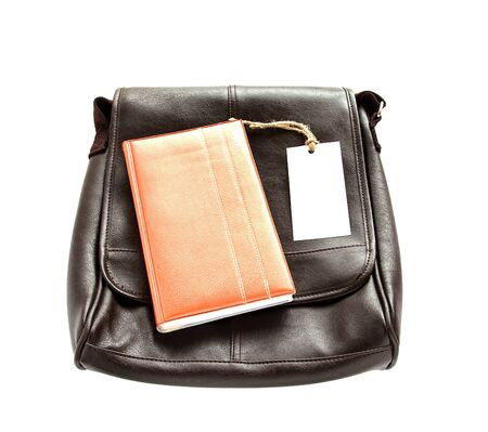 leather bag: Brown leather bag,notebook and white card on wooden table background