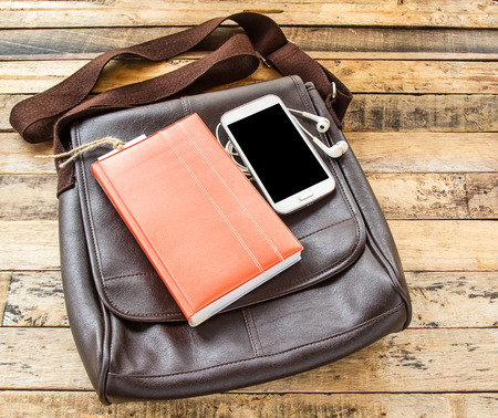 earphone: Brown leather bag,notebook,smart phone and earphone on wooden table background