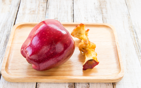 apple core: Red apple and apple core in wooden plate on white wooden background
