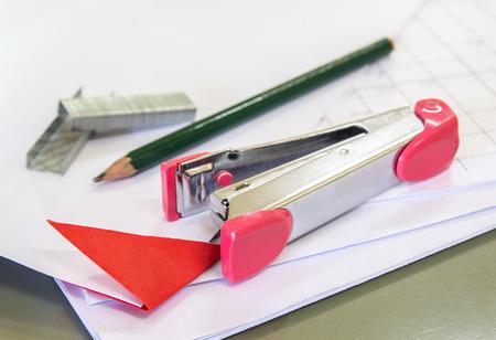 office stapler: Stapler with staples wires on white paper in office