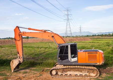 construction machinery: Excavator orange machinery, in the construction site. near high voltage power pole