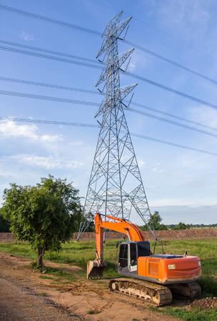 Excavator orange machinery, in the construction site. near high voltage power pole