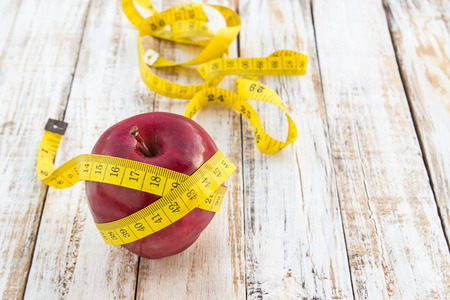 Red apple and yellow tape measure on a white wooden table background. Concept for healthy diet and body weight control.