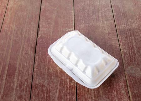 Espuma de poliestireno recipiente de comida en el fondo mesa de madera Foto de archivo
