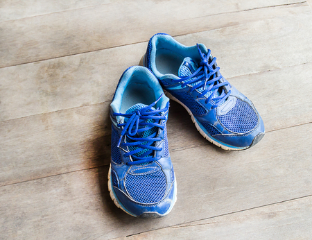 laid: blue running shoes laid on a wooden floor background Stock Photo