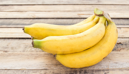 Fresh bananas on a wooden table background