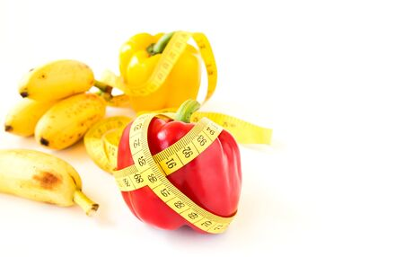 bell peper: Yellow tape measure and sweet pepper on white background. Healthy lifestyle concept