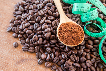 stimulating: Coffee powder in wooden spoon and coffee beans on wooden table background