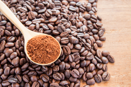 stimulate: Coffee powder in wooden spoon and coffee beans on wooden table background