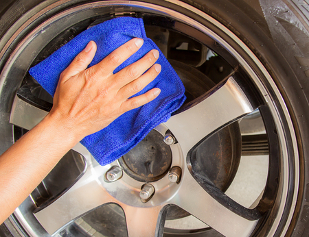 microfiber cloth: Hand with microfiber cloth cleaning wheel car.