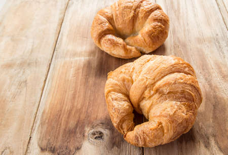 traditionally french: Fresh croissants on old wooden table background