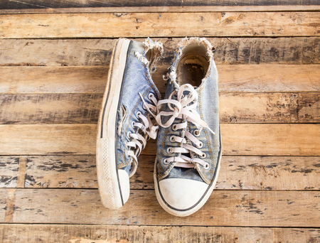 old shoes: Dirty old shoes on a wooden floor