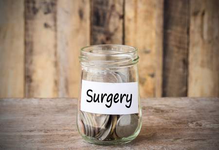 surgery expenses: Coins in glass money jar with surgery label, financial concept. Vintage wooden background