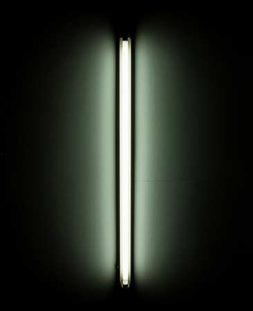 Detail of a fluorescent light tube mounted on a wall