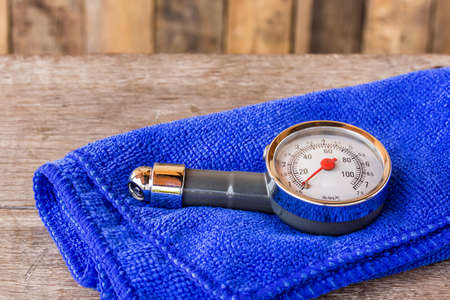 microfiber cloth: Tire pressure gauge and microfiber cloth on wooden table background