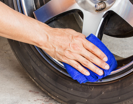 rag wheel: Hand with microfiber cloth cleaning a wheel car